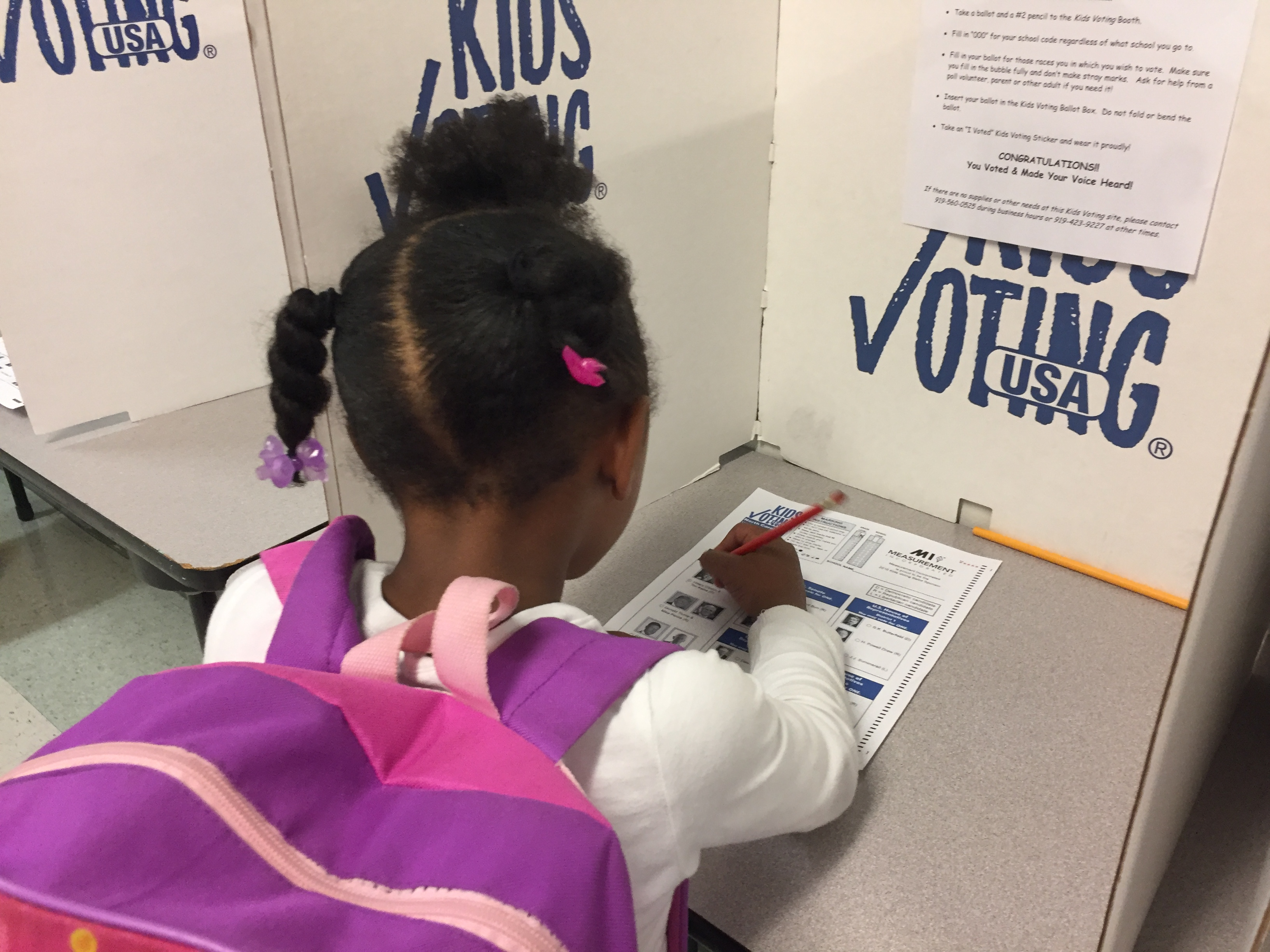 young girl in a child voting booth