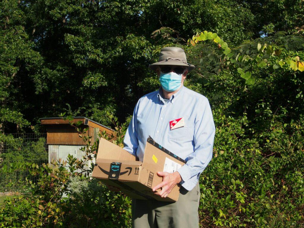 Volunteer holding box of vegetables