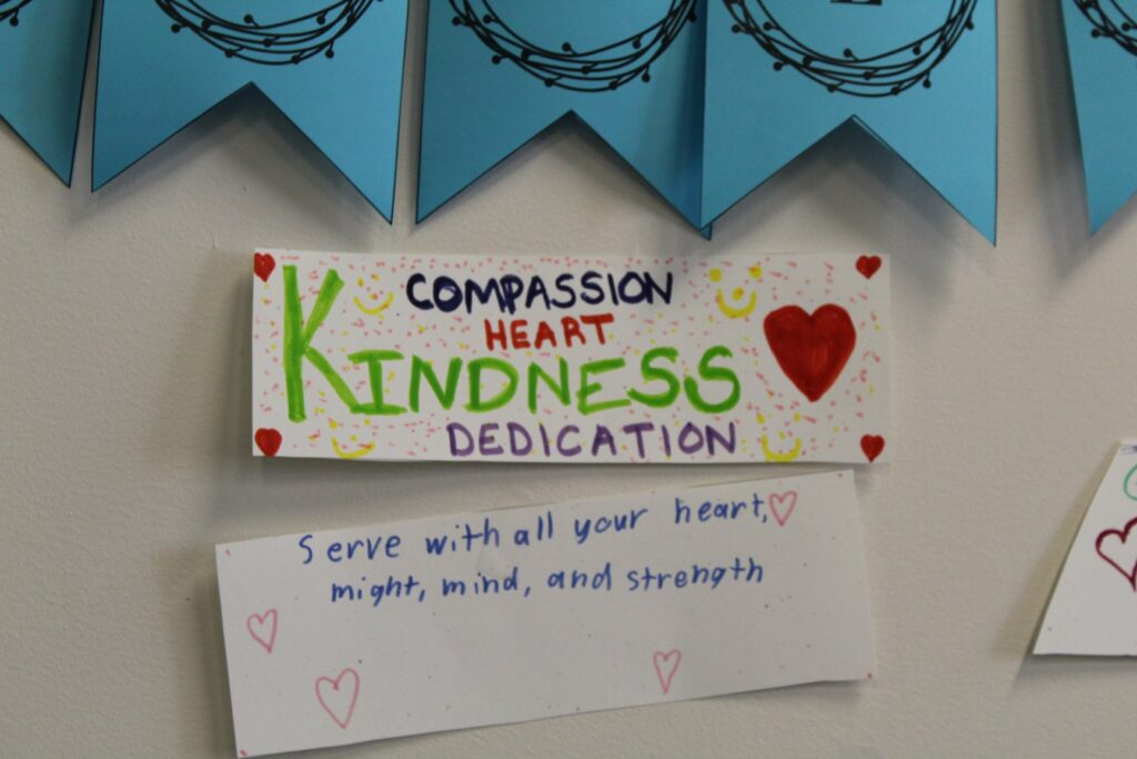 Picture of a sign that reads compassion heart kindness dedication