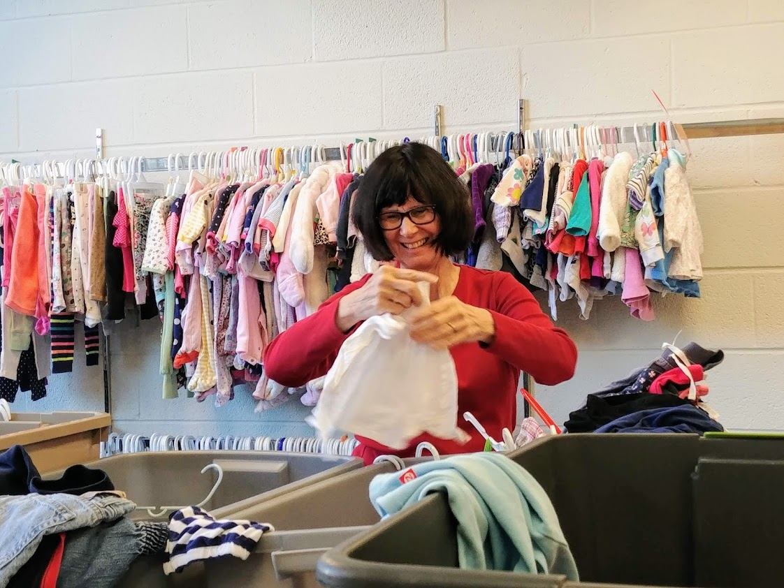 a woman volunteer sorting baby clothes