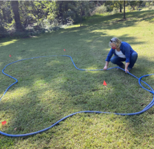 Master Gardeners mark the bed with garden hose