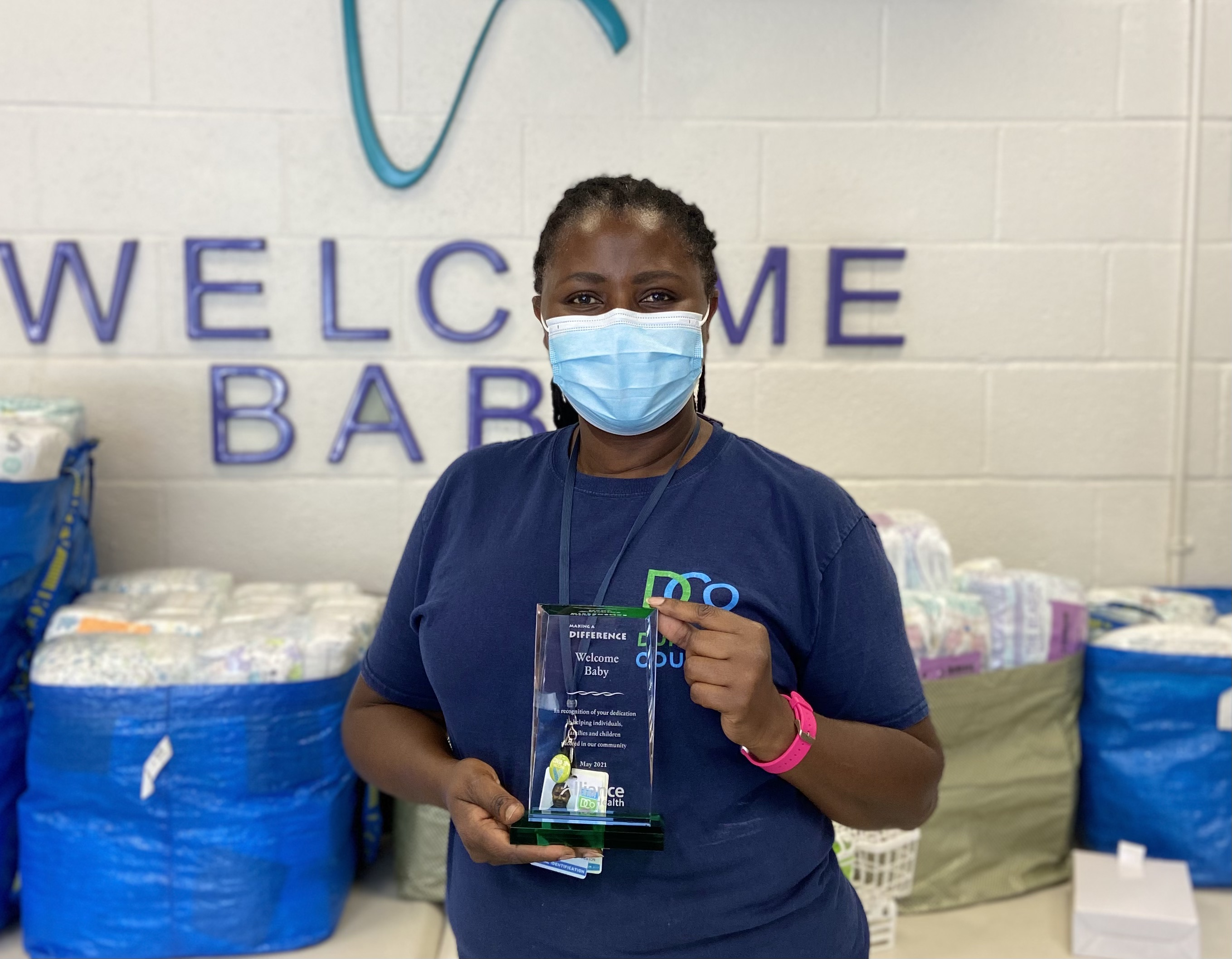 """Patience Mukelabai displaying The """"Making A Difference"""" Award from Alliance Health Plan"""