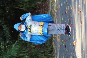Young boy in a blue Batman raincoat